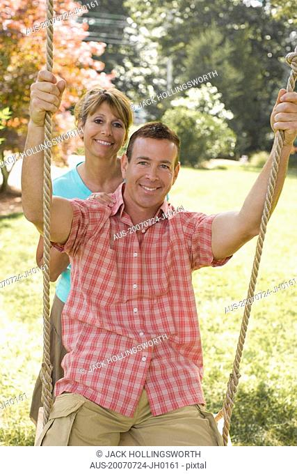 Portrait of a mature woman pushing a mature man on a rope swing