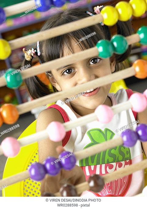South Asian Indian girl sitting in front of abacus in nursery school MR