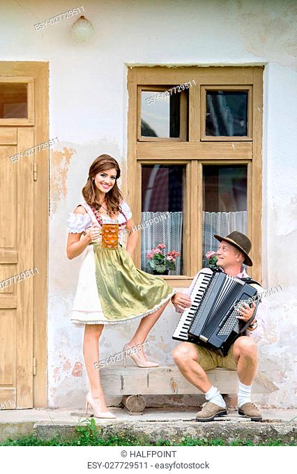Couple in traditional bavarian clothes standing against old country house, man playing accordion, woman holding a mug of beer. Oktoberfest