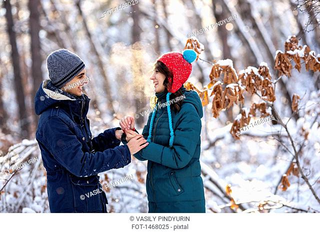 Playful young couple holding hands during winter