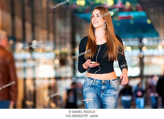 Young woman listening to smartphone music whilst strolling in shopping mall