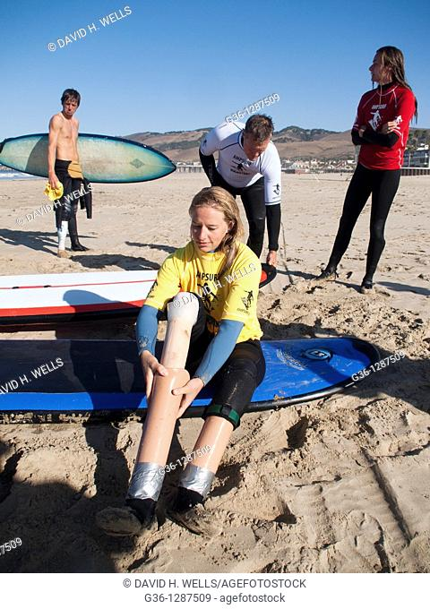 """Monica DeNatley, who was born without lower legs, empties water and sand from her """"surf legs"""" during the Surf Clinics sponsored by AmpSurf in Pismo Beach"""