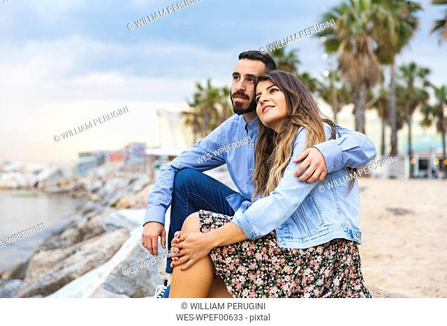 Spain, Barcelona, couple sitting on rocks at the seaside