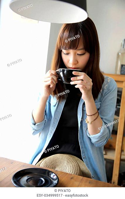 Asian girl indoor drinking coffee