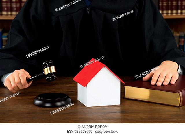 Midsection of judge with house model hitting gavel at desk in courtroom