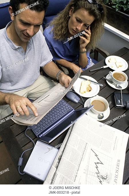 A young man and a young woman, couple, 25-30 30-35 35-40 years old, sitting on a balcony or terrace at a table having breakfast, working at a laptop and calling
