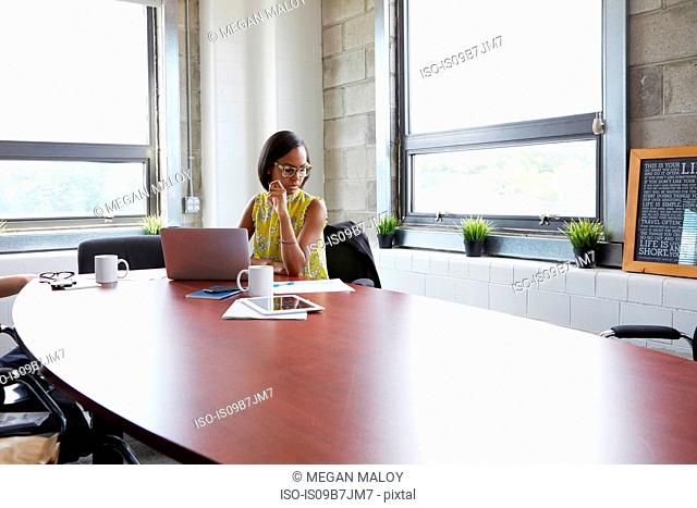 Young woman sitting at meeting room table, using laptop