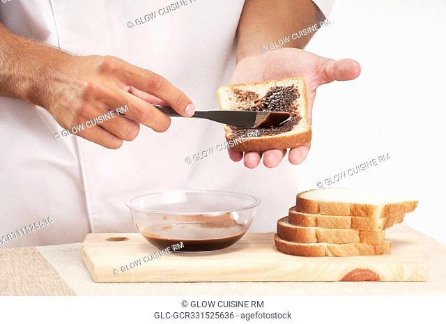 Man applying chocolate sauce on a slice of bread