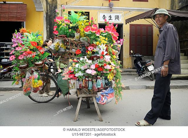 Asia, Vietnam, Hoi An  Hoi An old quarter  Street vendor selling flowers from his artfully overloaded bicycle  The historic buildings, attractive tube houses