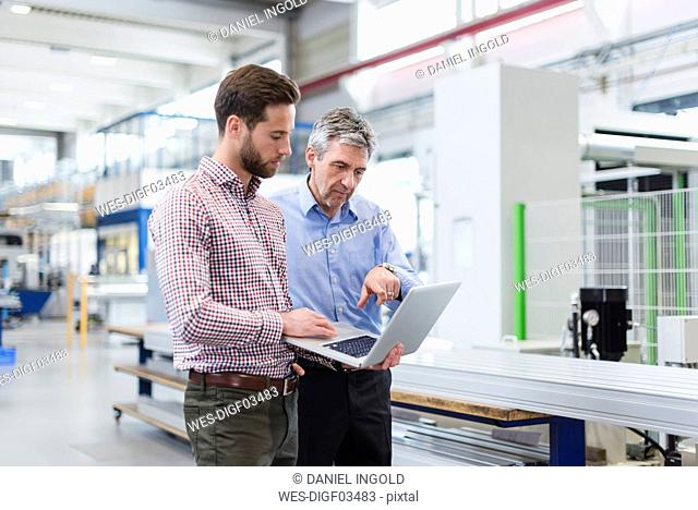 Businessmen using laptop in production hall