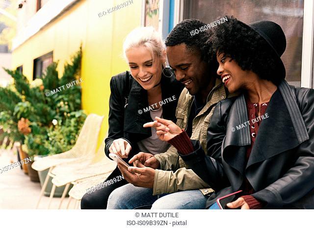 Friends in street looking at smartphone