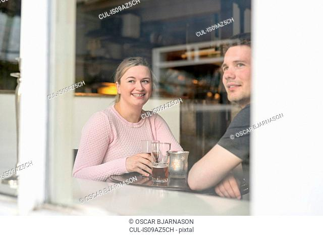 Young couple sitting in cafe, having drink