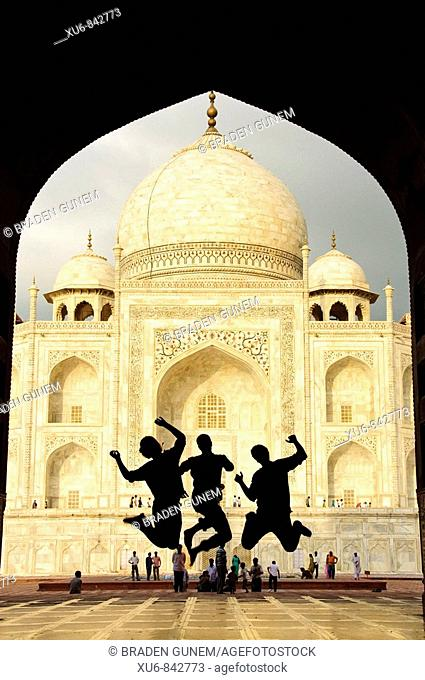 Tourist teens jumping in front of the Taj Mahal Agra, India