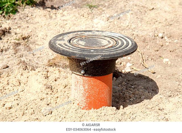 A orange sewer drainage pipe in a construction site