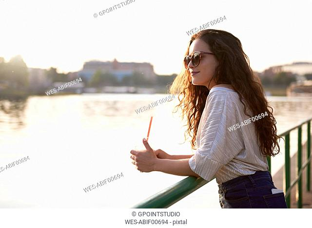 Smiling young woman with a takeaway drink enjoying the sunset at the riverside