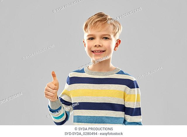 smiling boy in striped pullover showing thumbs up