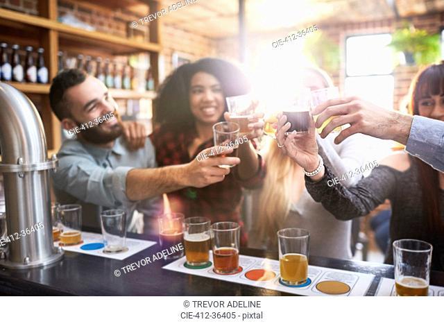 Friends beer tasting, toasting beer glasses in pub