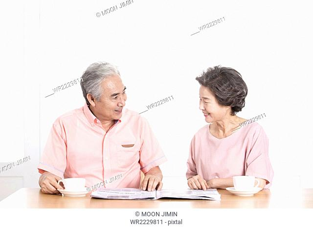 Portrait of old couple talking together face to face with newspaper at teatime