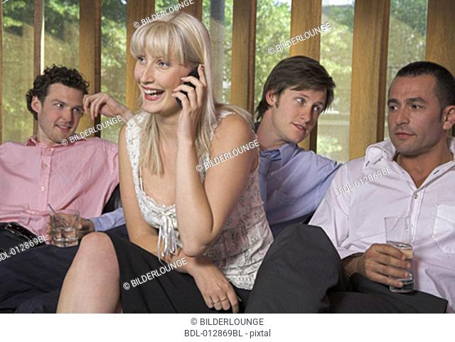 group of friends sitting together with woman having a conversation on her cellphone