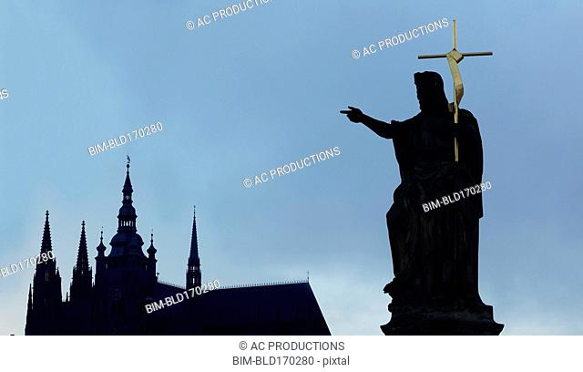 Silhouette of statue and crucifix by church spires, Prague, Bohemia, Czech Republic
