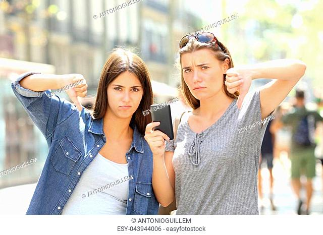 Two angry friends holding a smart phone with thumbs down in the street