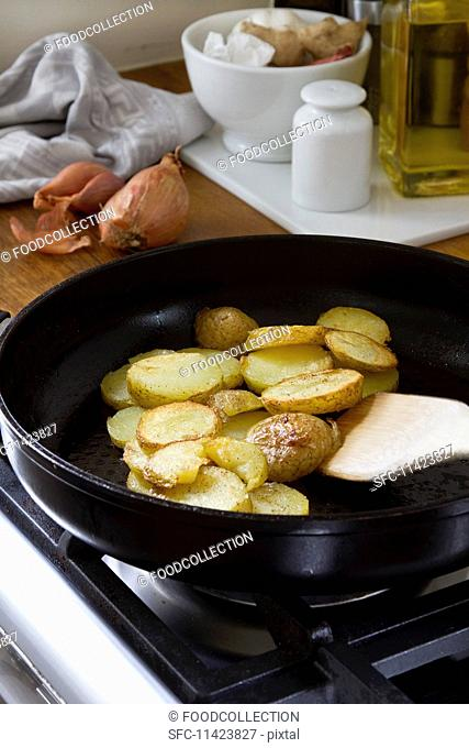 Sliced potatoes being fried in a pan