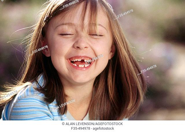Headshot of Happy Girl with missing teeth laughing