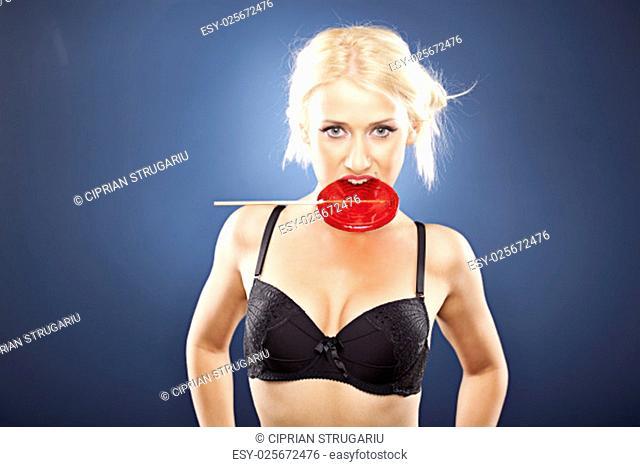Beautiful blonde model, in black bra, bites into a red lollipop