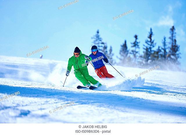 Two men skiing down snow covered ski slope, Aspen, Colorado, USA