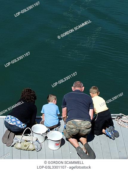 England, Cornwall, Falmouth. A family kneeling on a jetty fishing for crabs in Falmouth