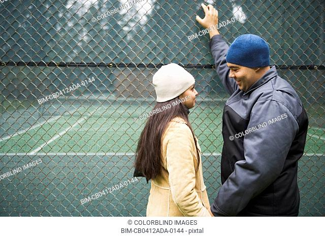 Couple talking by tennis court