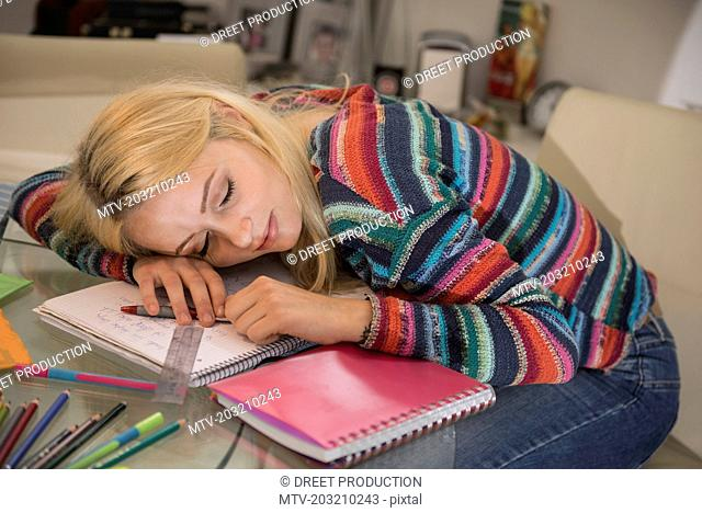 Exhausted student sleeping during doing homework in the living room, Bavaria, Germany