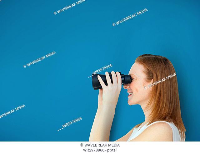 Happy woman looking through binoculars against blue background