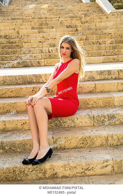 Sad blond woman sat on the steps outdoors