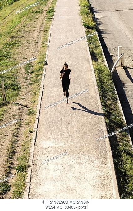 Sportive young woman running on a path