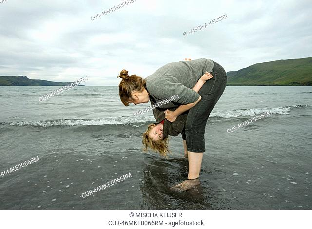 Mother and daughter playing in waves