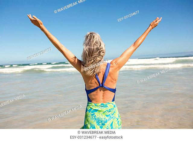 Rear view of senior woman with arms outstretched standing on shore