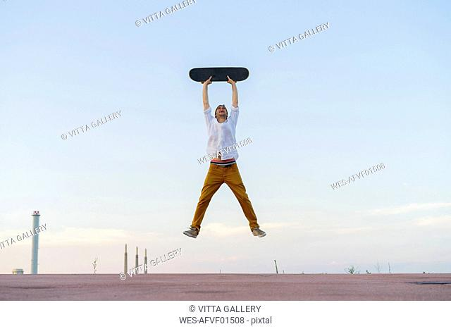 Young man jumping in the air holding a skateboard