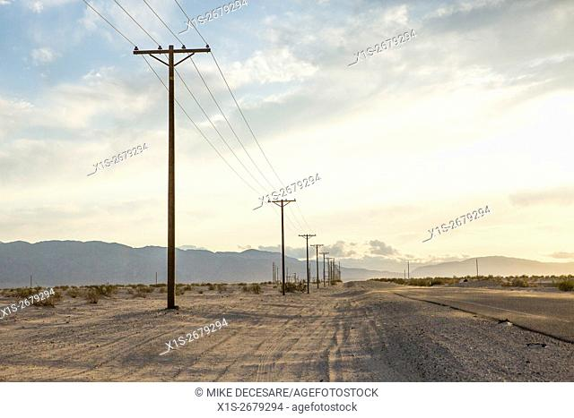 Drifting sand begins to cover roadway while power poles mark a border between desert and civilization