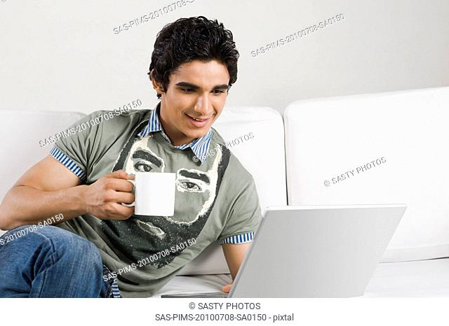 Man holding a cup of coffee and working on a laptop