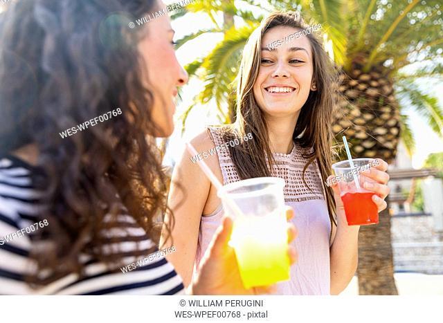 Two happy female friends enjoying a fresh slush