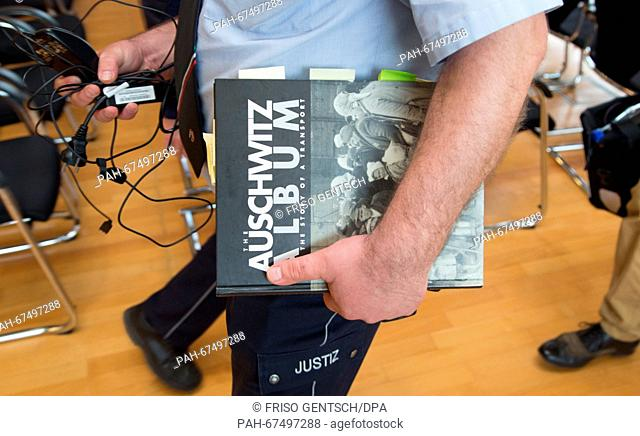 A judicial officer carries an edition of the book 'Auschwitz Album' after a trial hearing in Detmold, Germany, 15 April 2016