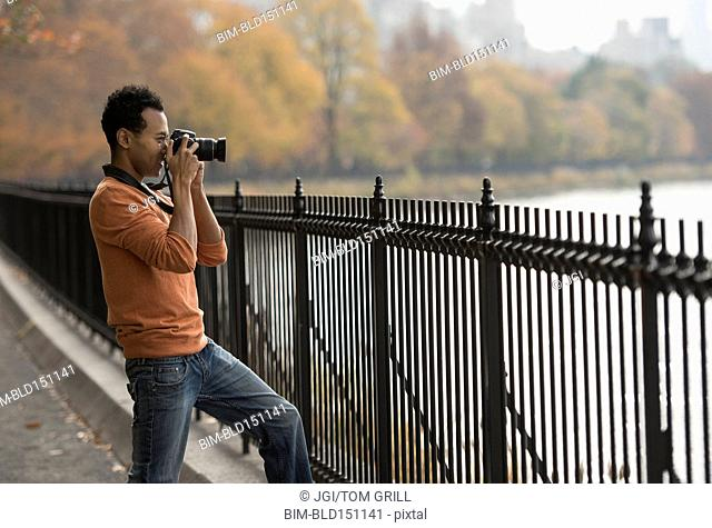 Mixed race man taking photograph on waterfront