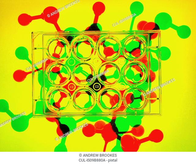 Photogram. Multiwell plates containing samples, molecular model of drug formula in background to illustrate ground breaking pharmaceutical research