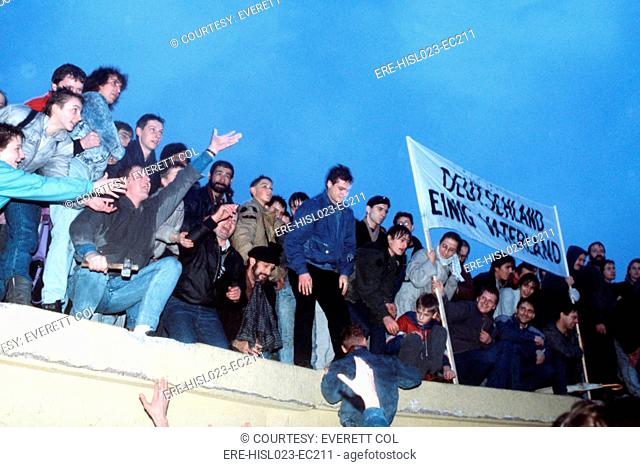 A crowd celebrates atop the Berlin Wall following the official opening of the Brandenburg Gate on Dec. 22 1989. BSLOC-2011-3-50