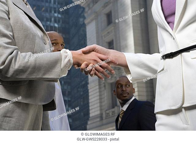 Mid section view of two businesswomen shaking hands
