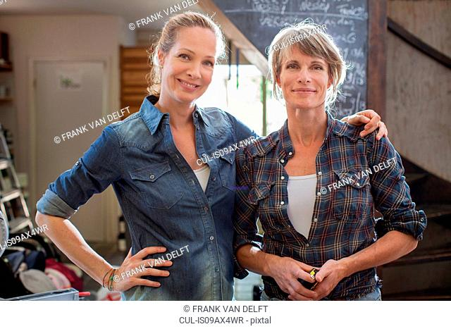 Portrait of women side by side looking at camera smiling