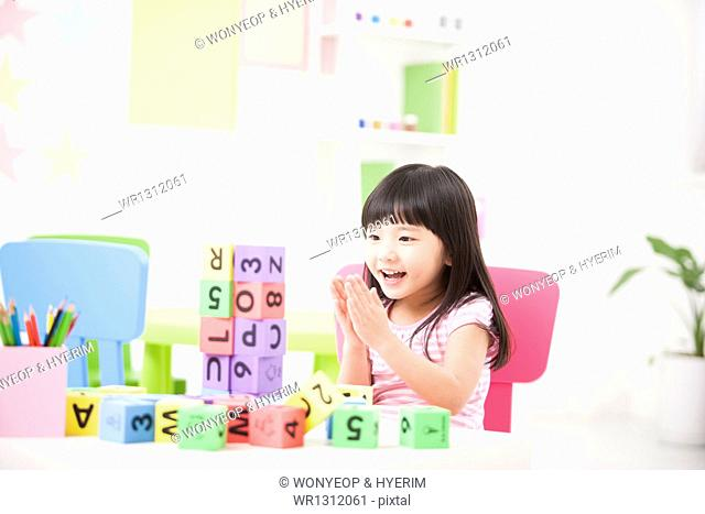 a kid playing with toy cubes on a table
