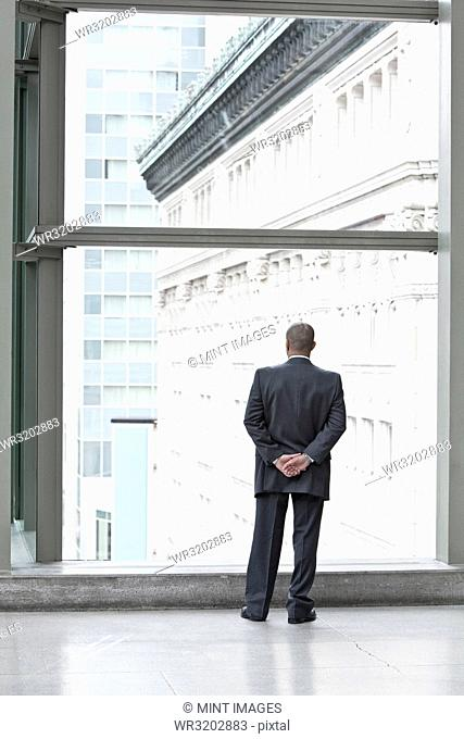 A businessman standing at a convention centre window looking out the window at the city in the background