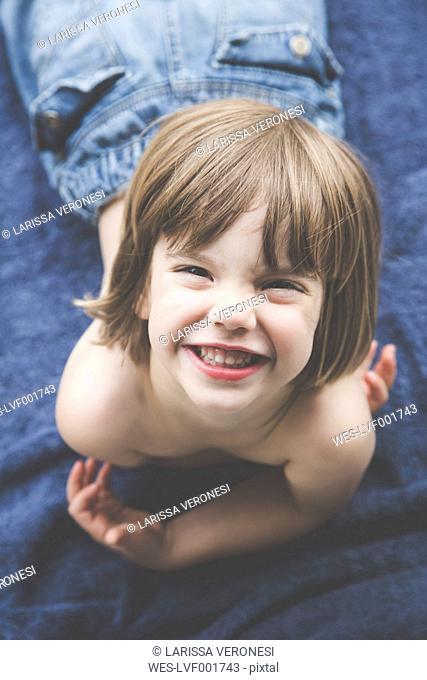 Portrait of grinning little girl lying on blue towel